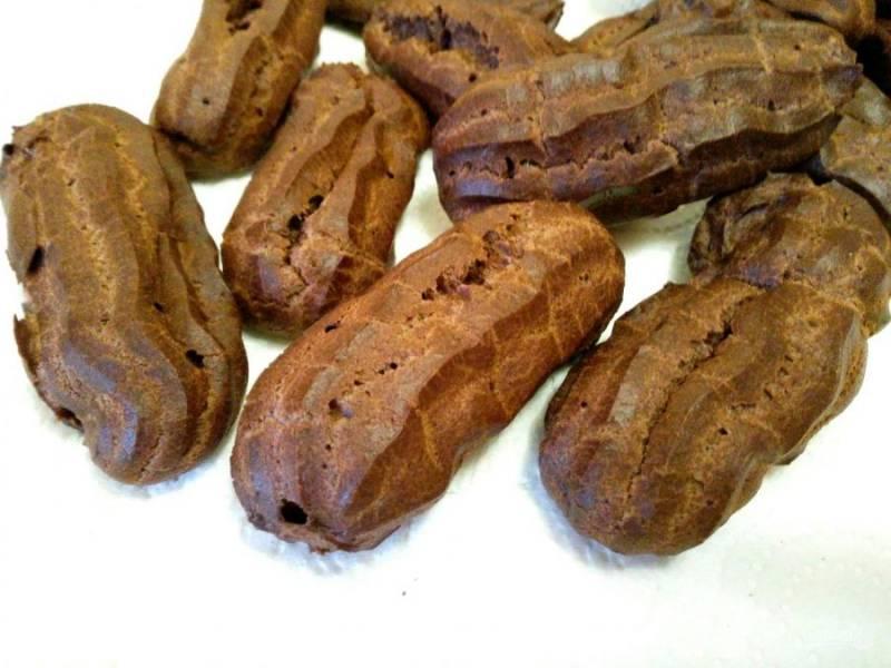 При выпекании пирожные из заварного шоколадного теста увеличиваются в размере, становятся воздушными. Снимите их с противня и остудите.