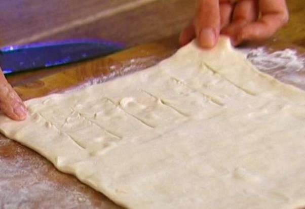 Размороженное пласты теста немного растяните. Один край (до середины) нарезаем широкими полосками, шириной 1,5–2 см.