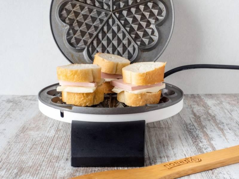 Вафельницу нагрейте и смажьте оливковым маслом. Это нужно делать перед каждой порцией бутербродов. На кусок багета с сыром и колбасой выложите сверху второй кусок багета. Разложите бутерброды в вафельнице.