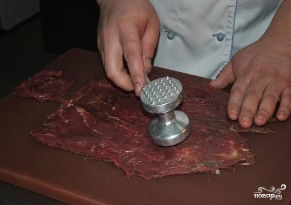 2. Выложите пласт говядины на рабочую поверхность и аккуратно отбейте молоточком. Лучше всего использовать вырезку. Посолите и поперчите кусочек с двух сторон.