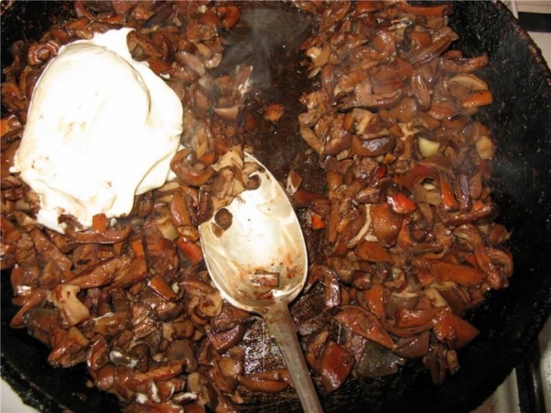 Обжариваем грибы в масле, солим и перчим. Добавляем сметану, тушим до готовности.
