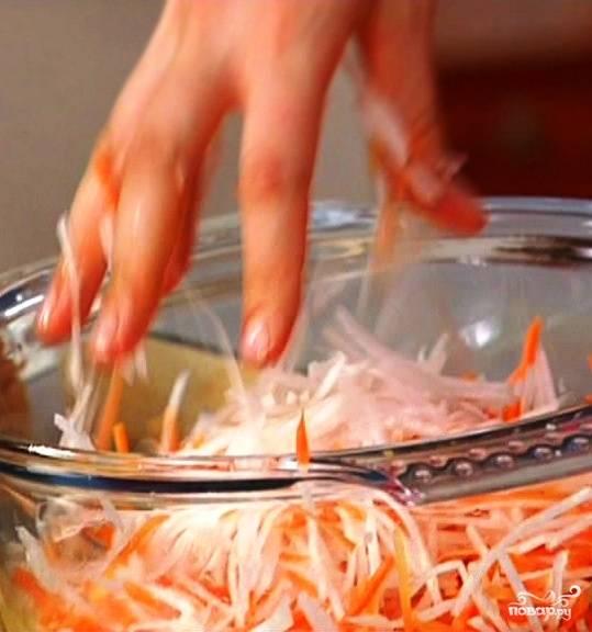 Аналогично шинкуем очищенную морковь. Рукой перетираем морковь и редьку, чтобы овощи пустили сок.