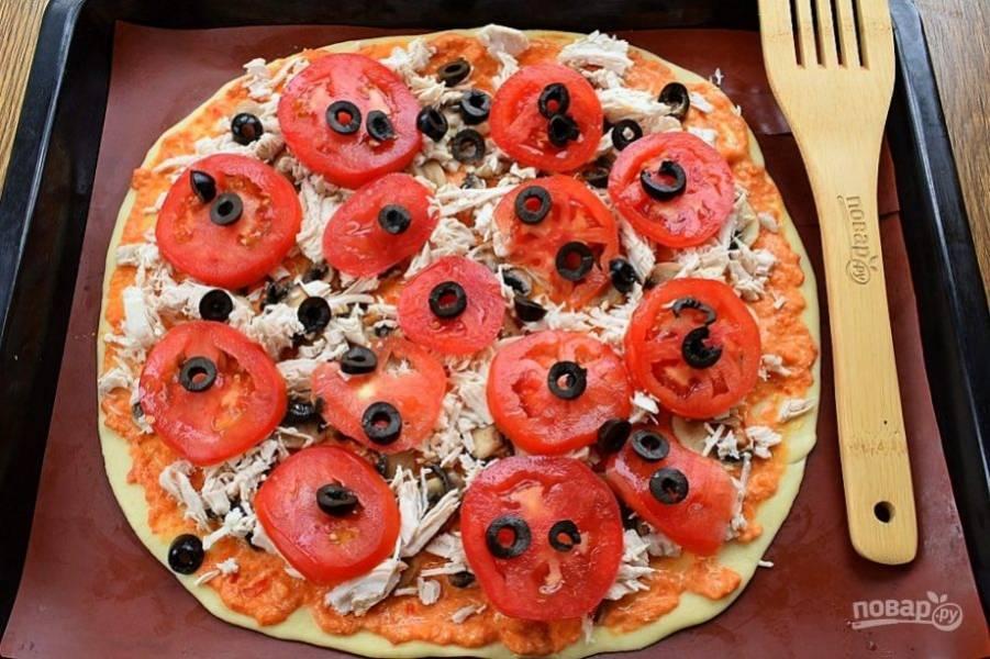 Сверху — измельченное куриное мясо, ломтики помидоров и колечки маслин.