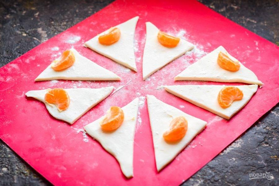 Слоеное тесто раскатайте, чтобы получился квадрат. Нарежьте тесто на небольшие прямоугольные заготовки. На край каждой заготовки выложите по дольке мандарина.
