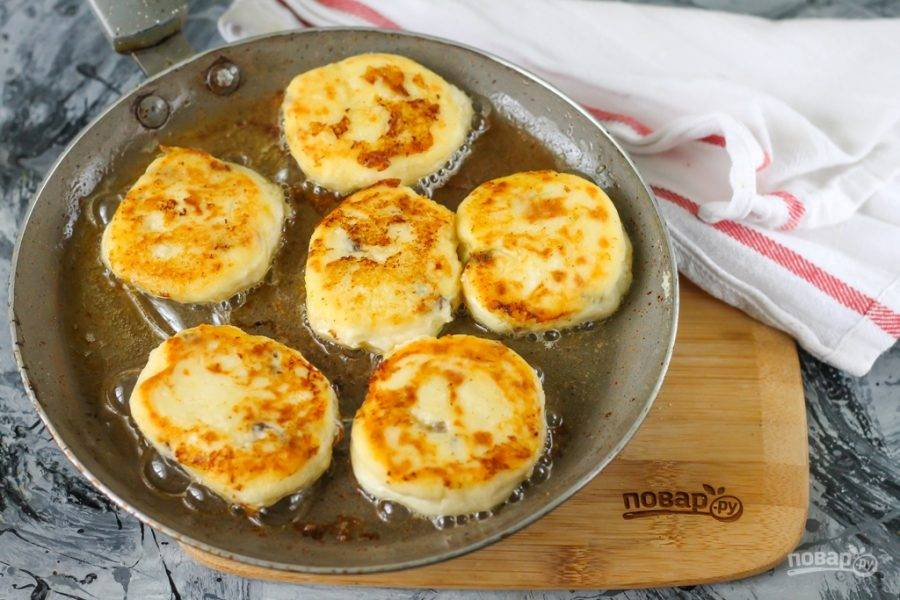 Аккуратно переверните сырники на другую сторону, обжарьте также до румяности около 2 минут.