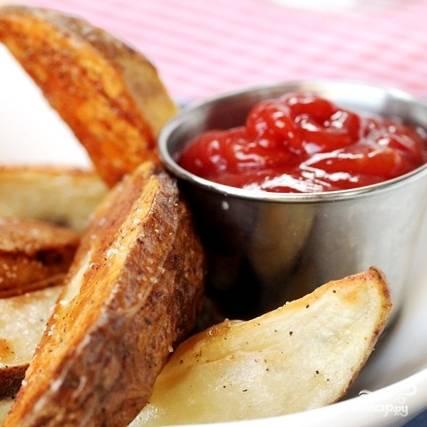 Запеченный в духовке картофель готов! На фото - вариант подачи, в качестве закуски, с кетчупом. Однако вы можете подавать такой картофель и как гарнир. Приятного!