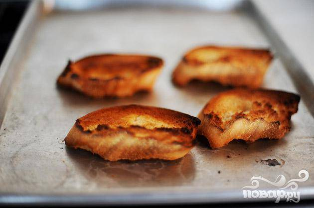 Запечь ломтики хлеба в духовке.