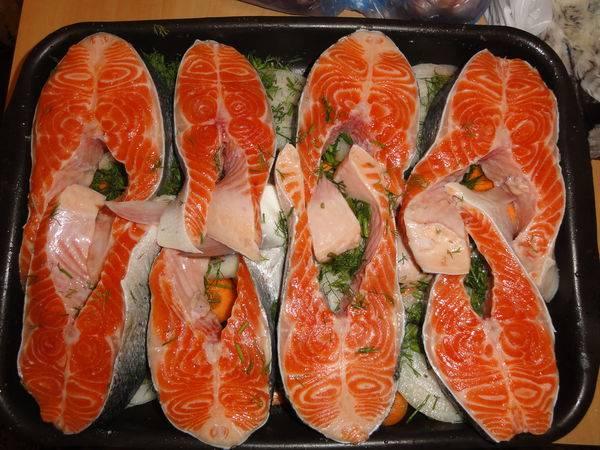 Смазываем противень растительным маслом и выкладываем по всей поверхности сначала лук, а затем морковь. Посыпаем укропом. Поверх овощей выкладываем стейки семги.