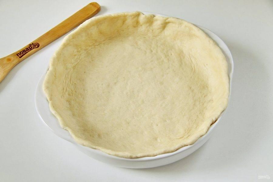 Большую часть теста раскатайте в форме круга  толщиной около 5-6 мм, с учетом бортиков около 2-3 см. Перенесите пласт раскатанного теста в смазанную маслом форму.