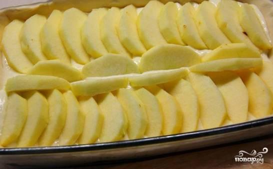 Поверх начинки выложите дольки яблок, их необходимо предварительно очистить.