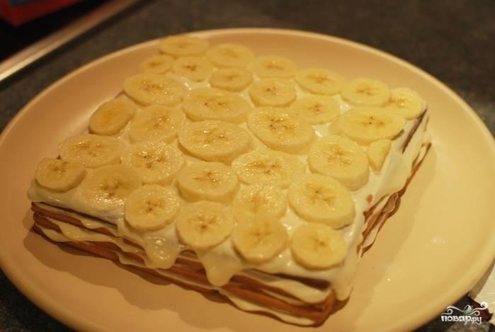 Четвертый слой намажьте творожной массой. Если используете творог, лучше предварительно взбить его в блендере, чтобы крупинок не было и он легче намазывался. Банан порежьте и выложите сверху на творог, потом — снова творожную массу поверх банана.