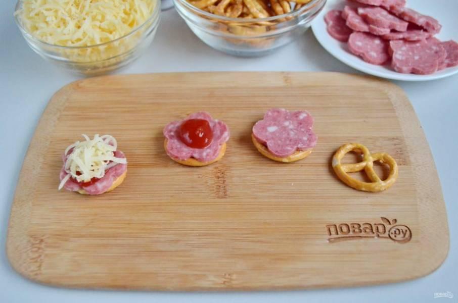 На претцель положите колечко колбаски, сверху капельку кетчупа и щепотку тертого сыра.