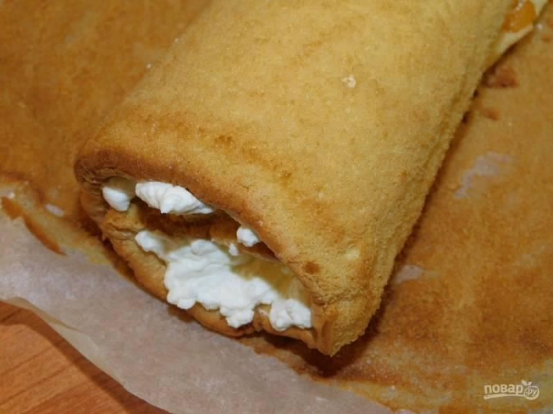 Остывший бисквит смажьте кремом и скрутите в рулет.