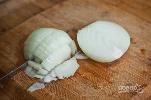 3. Пока варится бульон, можно заняться зажаркой. Очистите лук, измельчите и отправьте на сковороду с растительным маслом. Обжарьте до прозрачности, помешивая.