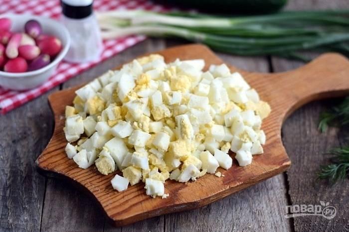 2.Яйца отварите в отдельной кастрюльке, затем остудите их под холодной водой и очистите от скорлупы. Нарежьте яйца кубиками.