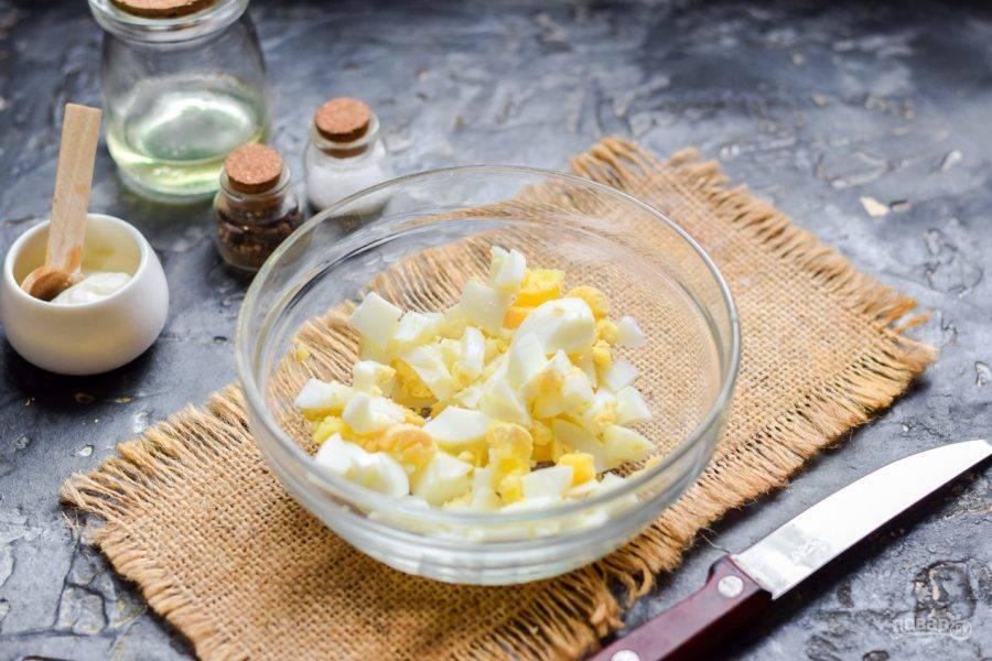 Куриное яйцо отварите 10 минут - вкрутую. Очистите яйцо, нарежьте небольшими кубиками. Переложите яйца в салатник.