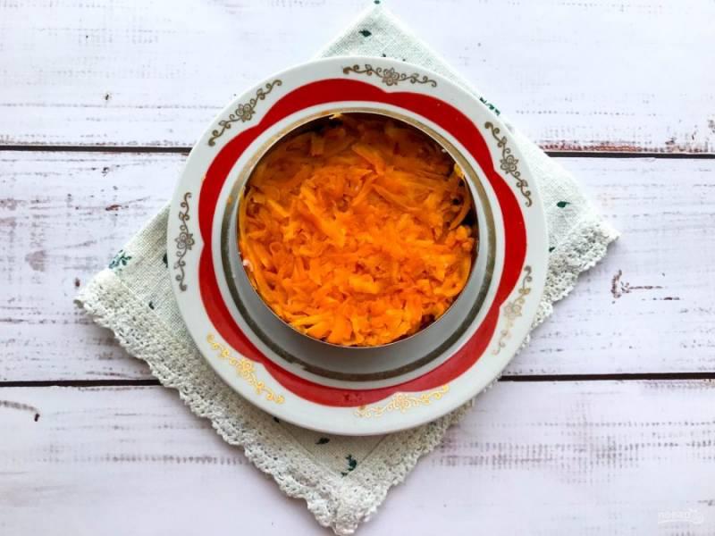 Морковь очистите, натрите на средней терке и выложите поверх лука.