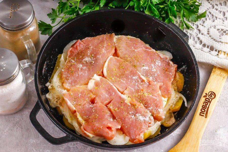 Мясо нарежьте тонкими широкими ломтиками и выложите на лук. Посолите, поперчите и присыпьте приправой для мяса. Желательно выбирать свинину с небольшой сальной прослойкой, чтобы мясо не получилось суховатым на вкус.