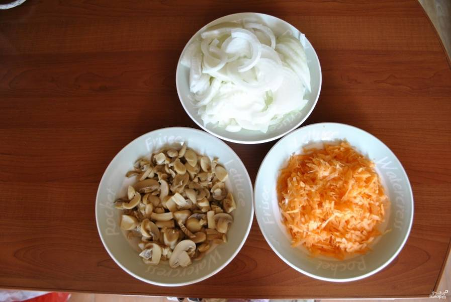 Порежьте лук полукольцами, можно и кольцами, если луковицы маленькие. Морковку натрите на терке, грибы порежьте кубиками или четвертинками. Обжарьте сначала лук в масле, потом добавьте морковку и грибы. Обжаривайте все на среднем огне, добавив специи, до готовности.