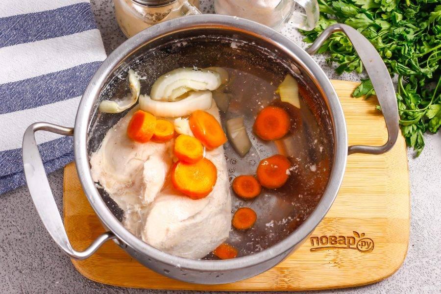Снова выложите грудку в кастрюлю, залейте горячей водой. Очистите от кожуры овощи, промойте и нарежьте. Выложите в кастрюлю вместе с лавровыми листьями. Добавьте соль.