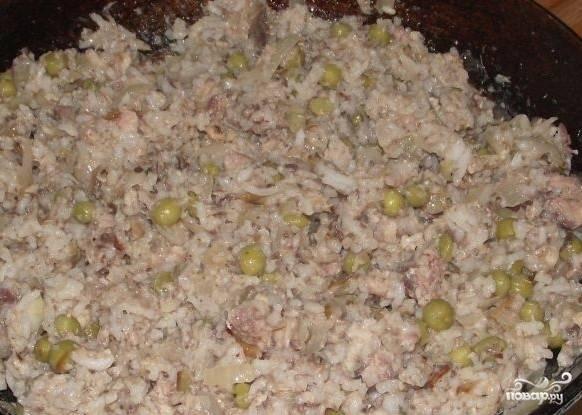 С рыбной консервы немного сливаем жидкость, разминаем рыбку вилкой до однородности, а дальше добавляем к рису на сковороде. Все хорошо перемешиваем, добавляем соль, перец по вкусу, еще можно добавить сухие ароматные травы. Убираем сковороду с огня, даем остыть нашей начинке для пирога.