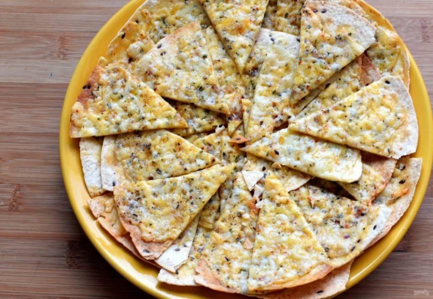 Выложите  кусочки тортильи внахлест в два-три слоя в огнеупорное блюдо, в котором можно подать пиццу на стол.