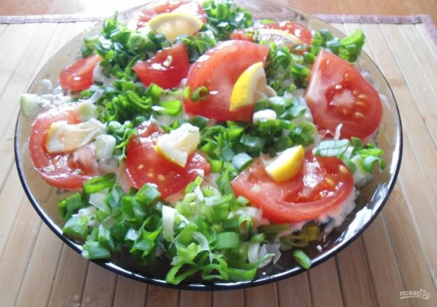 10.Посыпаю салат зеленым луком. Помидор мою и нарезаю крупными дольками, укладываю их на салат. Лимон нарезаю небольшими кусочками и выкладываю рядом с томатами. Приятного аппетита!