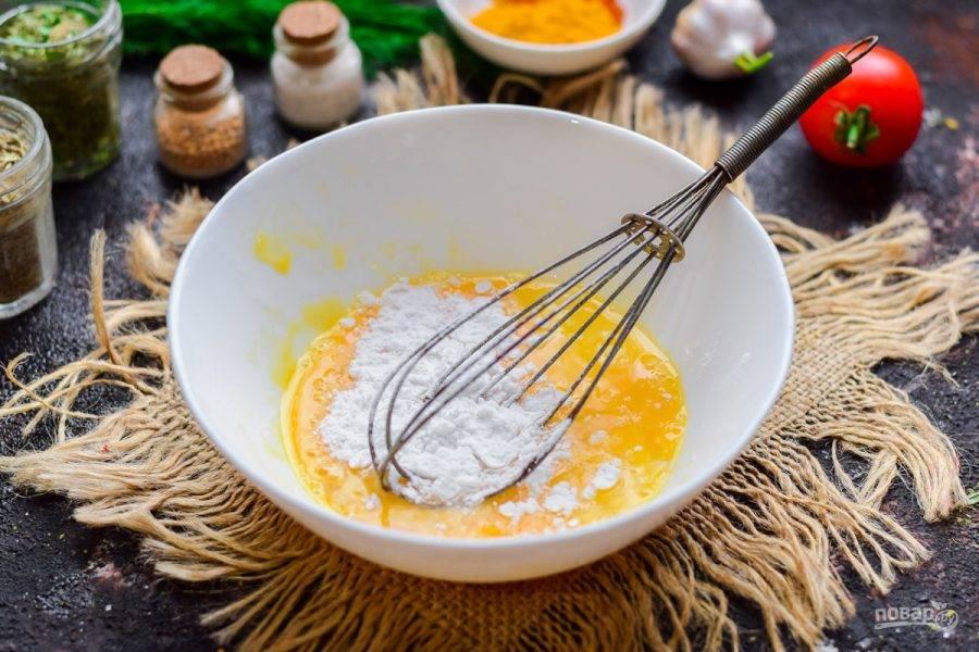 В миску вбейте куриное яйцо, добавьте крахмал, щепотку соли. Хорошо перемешайте все венчиком.