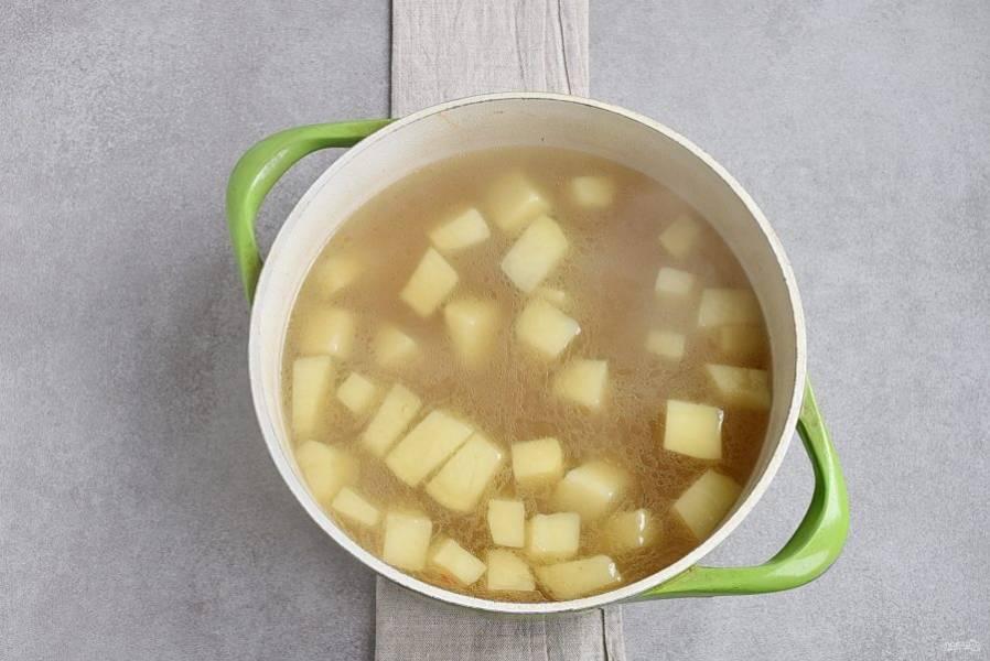 Опустите в бульон крупно порезанный картофель и поставьте отвариваться до полуготовности.