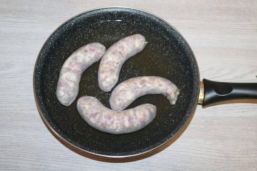 Свиные колбаски залейте водой, поставьте на огонь, варите 10-15 минут.