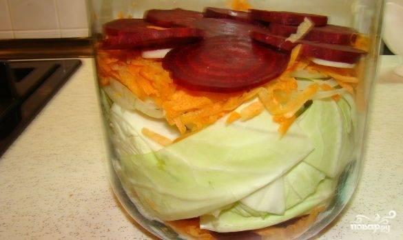 Подготовьте чистую сухую трёхлитровую банку. Туда уложите слоями: чеснок, лук, морковь, свеклу, капусту и ещё один слой. Заполните банку и слегка утрамбуйте овощи.