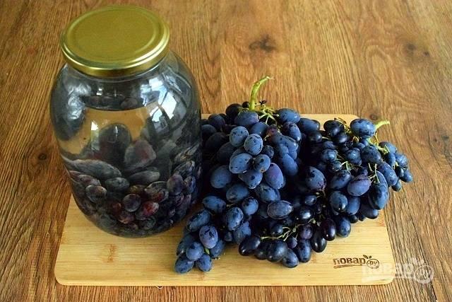 Сахар перемешайте с водой. Виноград переберите, снимите с веточки, удалите порченную ягоду. Промойте виноград в прохладной воде и заложите его в стерилизованные банки (2 л) на 1/3 их объема. Залейте виноград сладкой водой. Прикройте банки чистыми крышками.