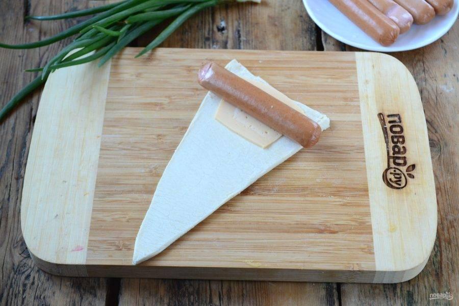 Каждый треугольник слегка растяните в длину. На каждый положите по тонкому ломтику сыра. Сверху положите сосиску. Края сосиски слегка надрежьте.