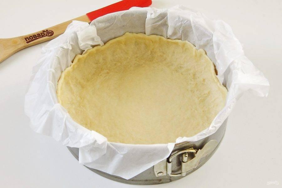 12. Форму застелите пергаментом и смажьте маслом. Тесто немного раскатайте и распределите в форме, формируя высокие бортики (у меня форма 20 см в диаметре).