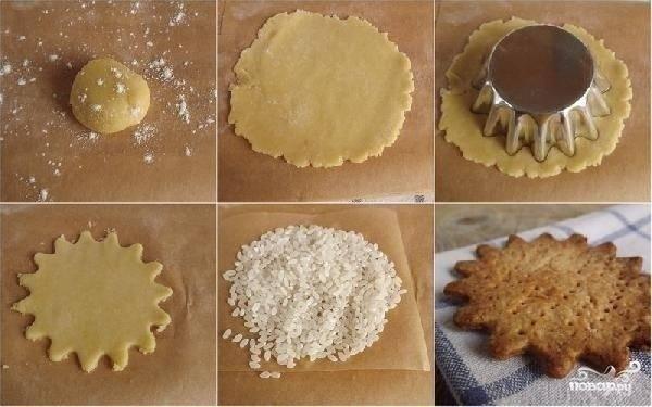Сначала следует приготовить песочное тесто. Для этого сливочное масло порубить с мукой в мелкую крупку, добавить желток и сахар. Замесить тесто до тугого состояния. Затем закрыть пленкой и положить в холодильник на 30 минут. Затем раскатать, вырезать форму, разложить тесто на противень, проколоть вилкой, закрыть бумагой для выпекания, насыпать сверху риса или бобовых (что бумага не слетела) и отправить в духовку запекаться на 10-15 минут (при температуре 200 гр).