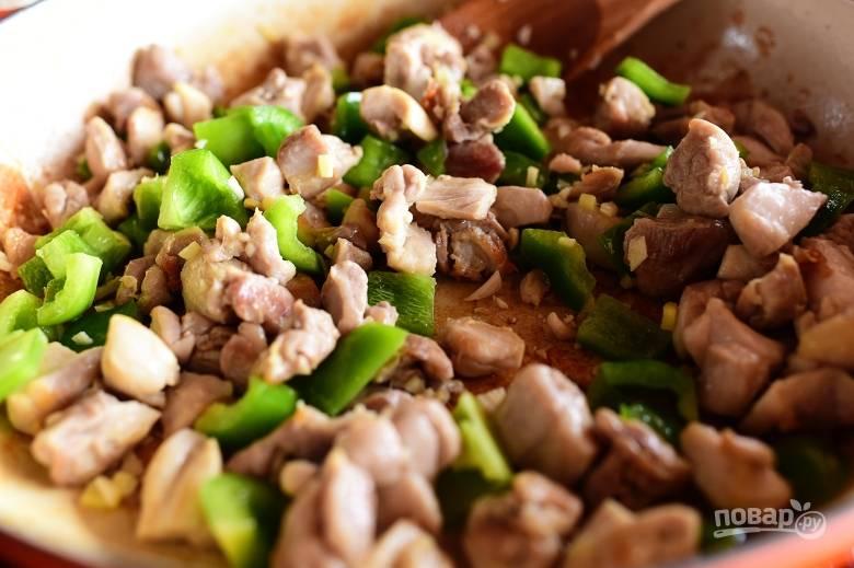 2. Добавьте к обжаренному мясу птицы измельченный болгарский перец, чеснок, имбирь и протушите 2-3 минуты.
