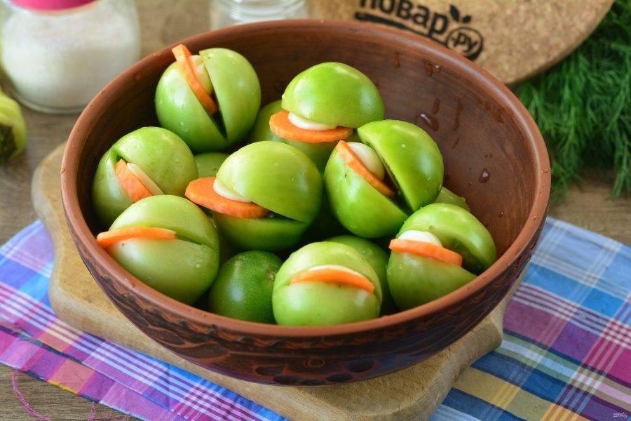 Разрежьте помидоры пополам, но не дорезайте до конца, чтобы помидоры держали форму. В разрез вложите по пластинке чеснока и морковки.