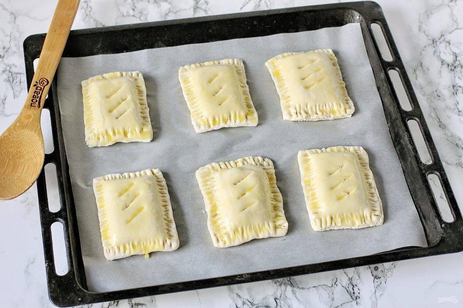 Готовые слойки переложите на противень, застеленный пергаментом и смажьте желтком. Выпекайте в духовке при температуре 180-200 градусов около 20 минут.