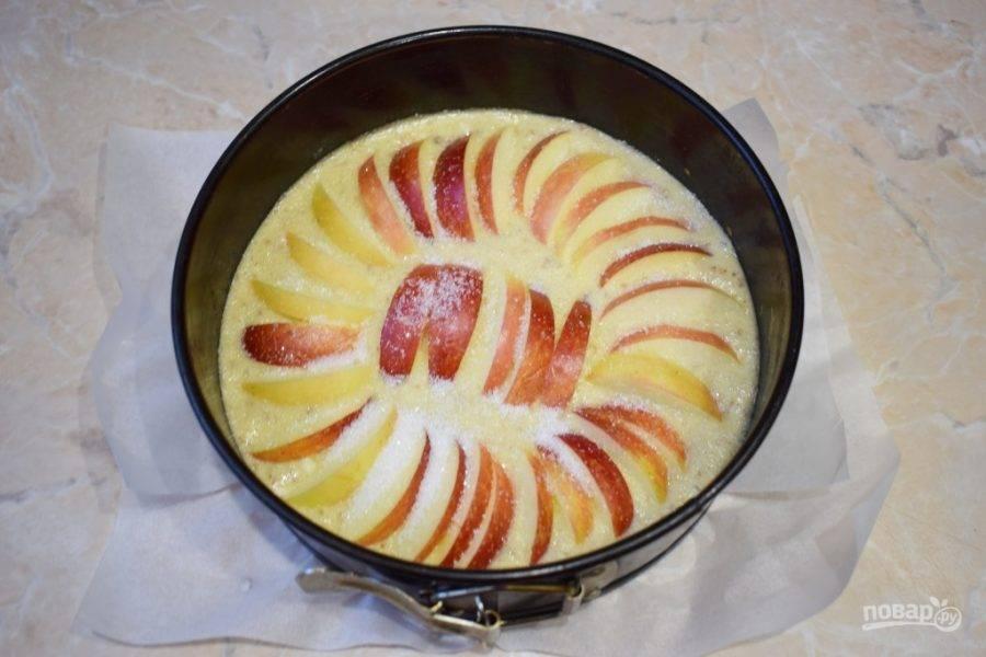 Яблоки нарежьте ломтиками и разложите по всей поверхности пирога. Сверху посыпьте пирог небольшим количеством сахара. Поставьте пирог в духовку разогретую до 180 градусов примерно на 40 минут.