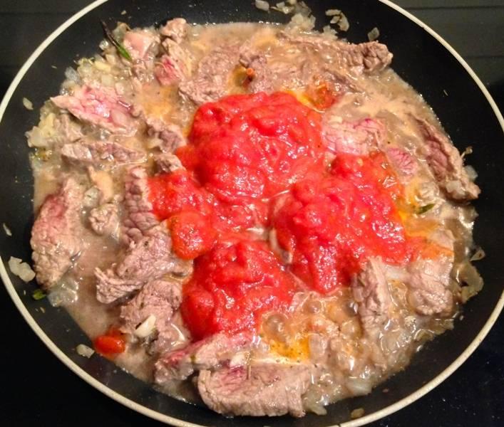 За это время мы бланшируем помидоры в кипятке, очищаем их от кожицы и измельчаем в блендере до состояния пюре. Выкладываем томатную пасту на сковороду к мясу, перемешиваем все и тушим 5 минут.