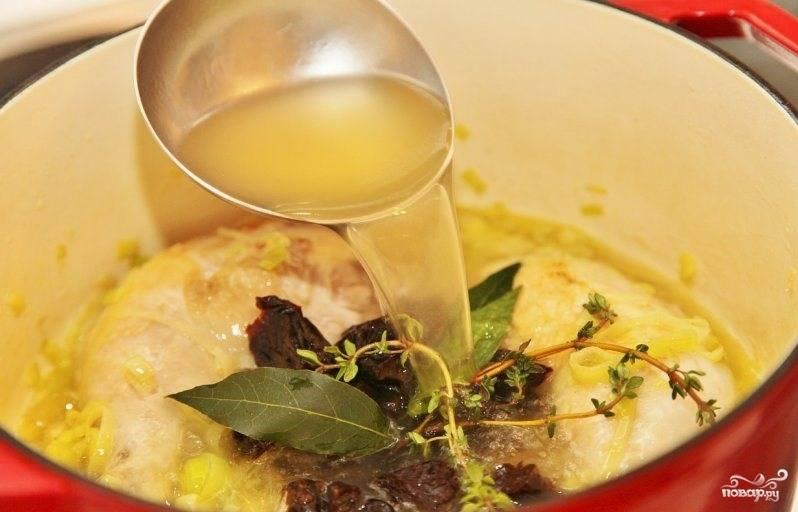 Затем к курице и луку добавляем нарезанный чернослив (предварительно запаренный), лавровый лист, веточки тимьяна. Заливаем бульоном.