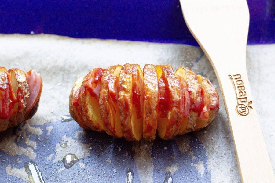 Когда картофель будет готов, вставьте кусочки колбасы в разрезы и полейте картофель кетчупом.