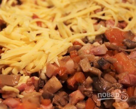 Натрите в сковороду половину сыра. Перемешайте ингредиенты. Готовьте их на огне ещё 3 минуты.