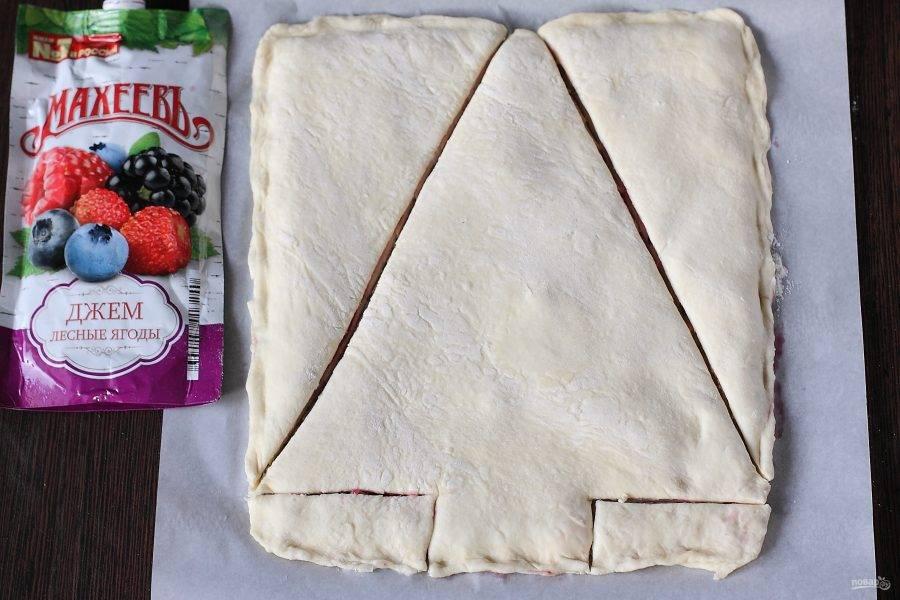 Из получившегося прямоугольника сформируйте елочку. Нижнюю часть обрежьте в форме ствола, затем обрежьте пирог в форме треугольника. Обрезки можно запечь отдельно, нарезав порционными кусочками.