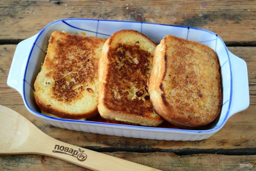 Дно формы для запекания слегка смажьте томатным соусом. Выложите все три бутерброда.