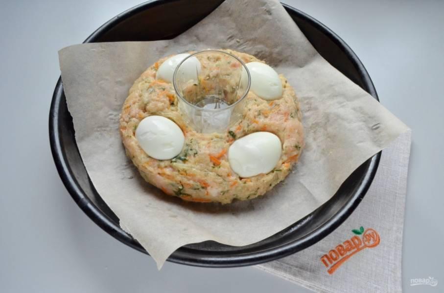Вареные яйца порежьте на половинки. Вдавите их в тесто хорошо.