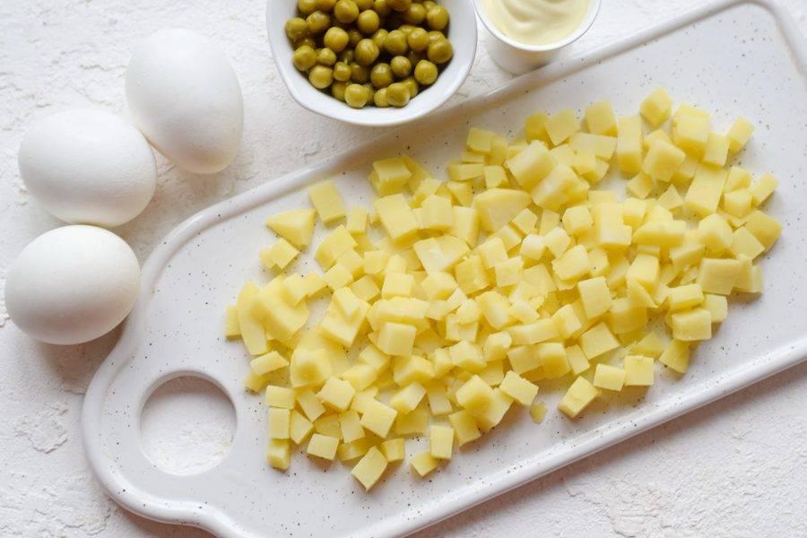 Картофель варите в кожуре примерно 15-20 минут после кипения воды. Клубни остудите, очистите, нарежьте ровным кубиком среднего размера.