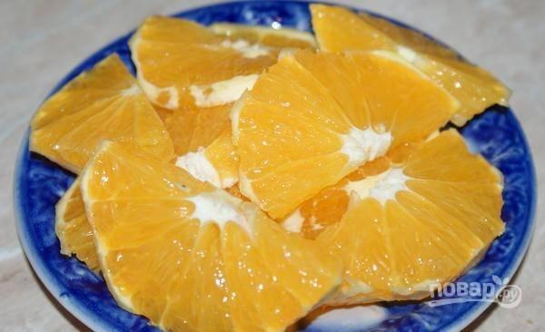 Мякоть второго апельсина нарежьте кружками, а затем каждый разделите пополам.