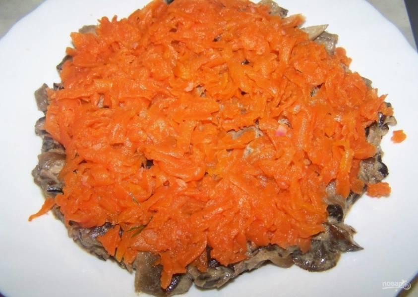 3.Готовую морковь чищу и мою, затем натираю на крупной терке, выкладываю следующим слоем, немного солю и перчу.