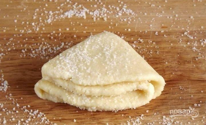 Сложите каждый кружок пополам. Снова присыпьте их сахаром. Опять сложите тесто пополам, чтобы получилось что-то наподобие треугольников. Присыпьте их сахаром еще раз.
